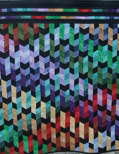 <p>Rainbow Diamonds 2012 <p>Bargello style piecing in bright colours. Colour choice mine, design by Jan Hassard. Machine quilting of oval shapes to contrast with diamond piecing. Space dyed thread in bright colours used for the quilting.
